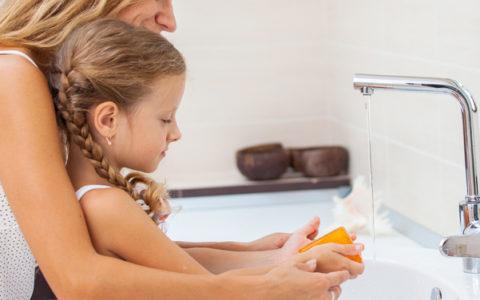 Mom and daughter at sink handwashing