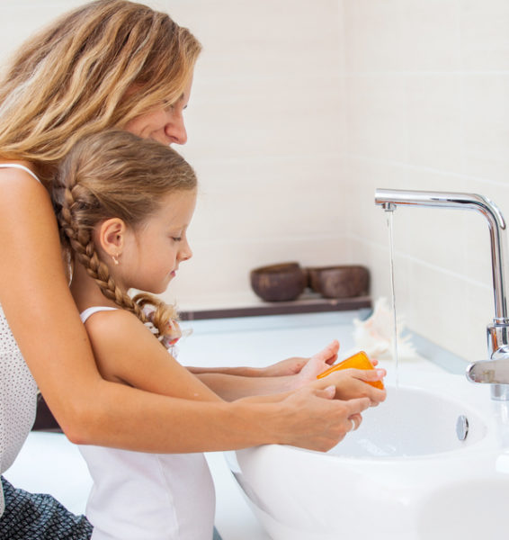 Mom and daughter at sink handwashing